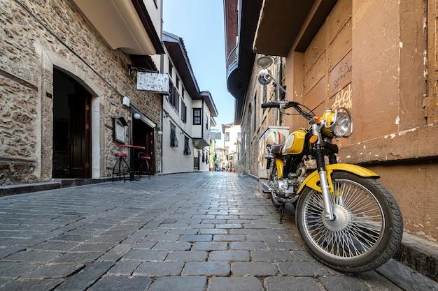 Уютные улочки калеичи в анталии мотоцикл припаркован на пустой уютной улочке. тишина и покой в историческом центре анталии в турции. путешествие и туризм.