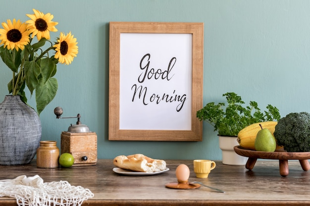 Cozy and stylish composition of creative dining room with poter frame, wooden consola, sunflowers and personal accessories. green wall. beautiful and sunny morning.