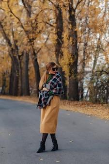 秋のカラフルな公園で居心地の良いスタイリッシュな若い女の子の散歩