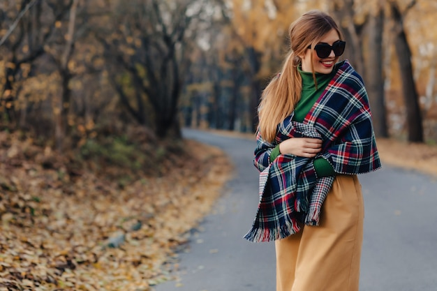 Cozy stylish young girl walk at autumn colorful park