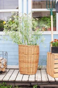 아늑한 여름 장식 베란다 집 시골집 벽에 꽃이 있는 고리버들 바구니