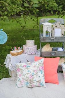 居心地の良い夏の写真ゾーン、ロマンチックなレクリエーションエリア、またはピクニック。白い毛布でピクニック、カラフルな明るい枕、お菓子、花
