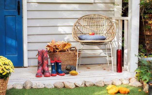 의자, 격자 무늬, 고무 장화가있는 아늑한 여름 테라스. 가을 나무 현관 집. 휴식을위한 아늑한 테라스