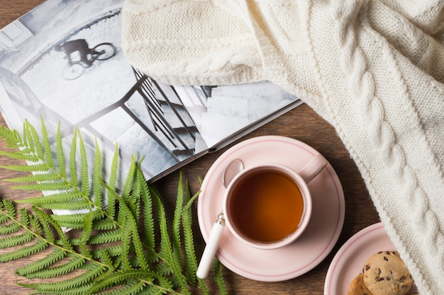 Cozy sweater; book; tea cup and cookies with leaves on table