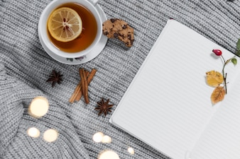 Cozy teatime with notebook on knitted cloth