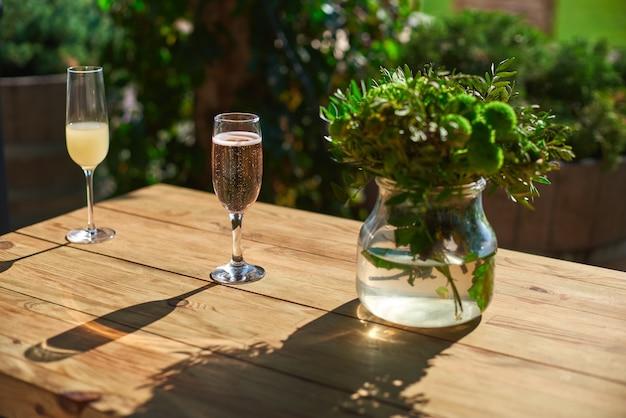居心地の良いテラス、木製のテーブルにシャンパンとガラス