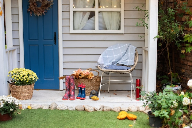 Уютная терраса со стульями, пледом, резиновыми сапогами, корзинами с хризантемами. украшения в патио для отдыха. стильный декор на крыльце дома.