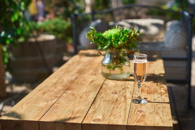 休憩用のソファ付きの居心地の良いテラス、木製のテーブルにシャンパン付きのガラス
