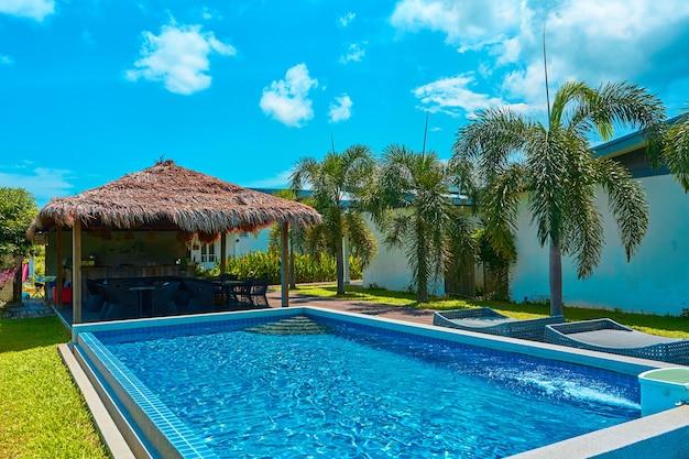 Уютный тропический курорт с бассейном на заднем дворе. яркий солнечный день