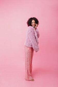 핑크 색상의 아늑한 세로 샷. 스트라이프 와이드 바지와 모피 코트를 맨발로 입은 소녀가 얼굴에 뻣뻣하게 닿습니다.