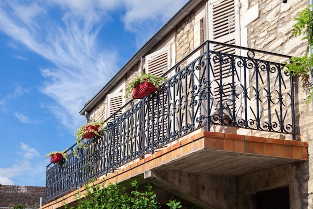 Cozy vintage french balcony with black metal railings, flowers in pot, open shutters on windows against blue sky, clouds.
