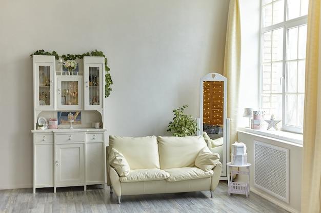 나무 찬장과 베개, 바닥 거울 및 대형 조명 창이있는 흰색 소파가있는 아늑한 빈티지 거실 인테리어