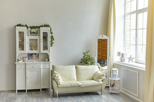 Cozy vintage living room interior with wooden sideboard and white sofa with pillows, floor mirror and large light window
