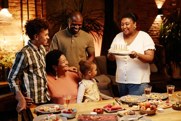 Cozy warm toned portrait of happy africanamerican family celebrating birthday together indoors at ev...