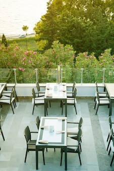 A cozy wicker table in the outdoor cafe-bar on the rooftop in the morning with view on a sea,