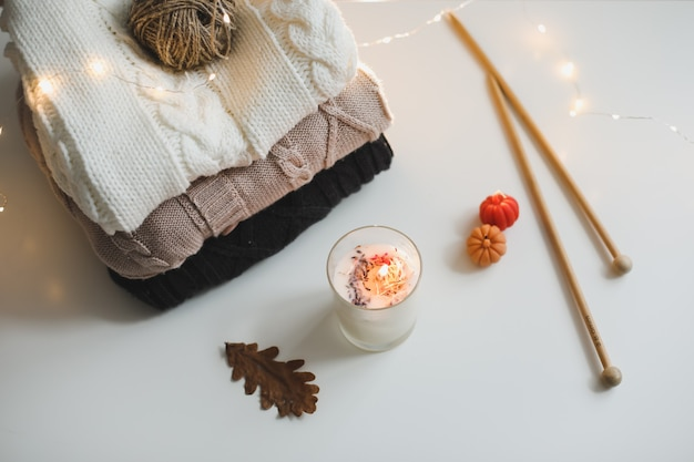 Cozy winter and autumn composition with needles knitted clothes and a candle top view