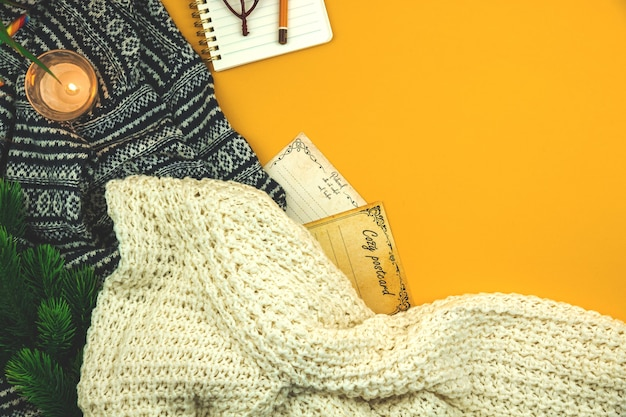 Cozy winter and autumn yellow background with woolen and knitted sweater, postcards and candles, flat lay and top view. high quality photo photo