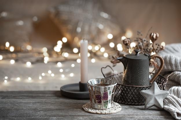 Accogliente sfondo invernale con dettagli di decorazioni per la casa su uno sfondo sfocato con luci copia spazio.