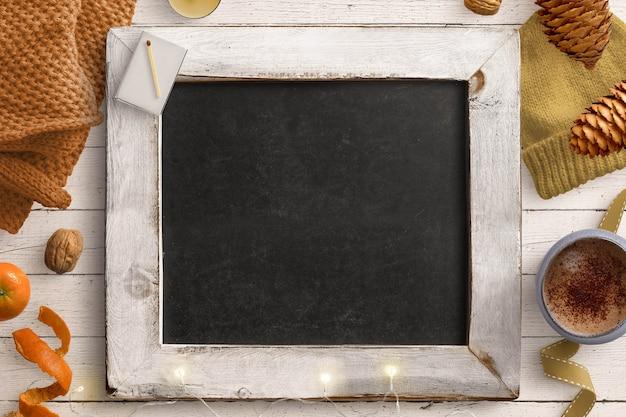 Cozy winter blackboard scene with fairy lights, woollen items, pinecones and hot drink