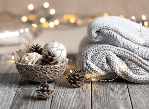 Уютный зимний фон боке с сложенными свитерами и деталями декора.