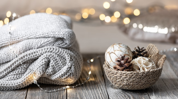 Cozy winter bokeh background with stacked sweaters and decor details