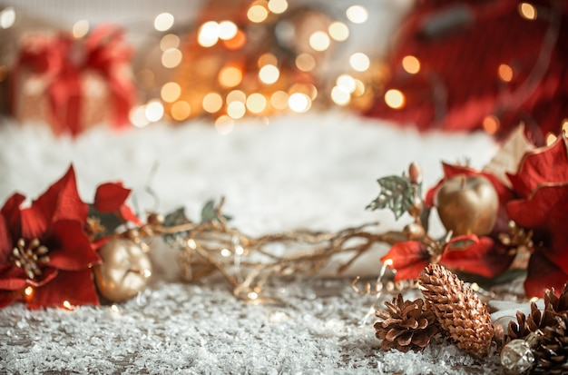 Cozy winter christmas wall with snow and decorative pine cones on blurred colorful wall.