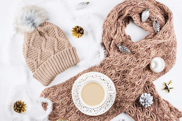Cozy winter clothing, hot drink and christmas decorations frame