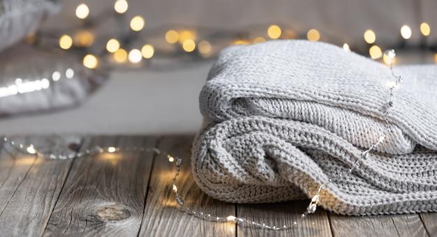 Уютная зимняя композиция со стопкой вязанных предметов на размытом фоне с боке, копией пространства.