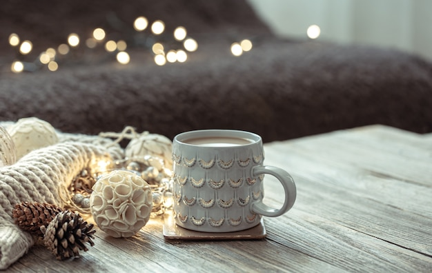 Cozy winter composition with a cup and decor details on a blurred background.