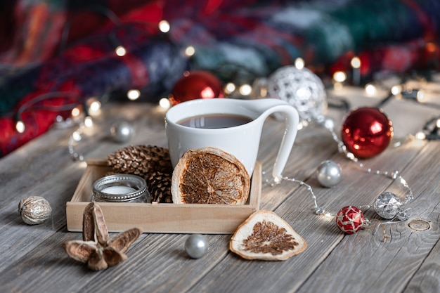 Composizione invernale accogliente con una tazza di bevanda calda, dettagli decorativi e palle di natale su uno sfondo sfocato con bokeh.