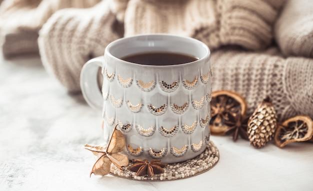 Accogliente composizione invernale con una tazza e un maglione