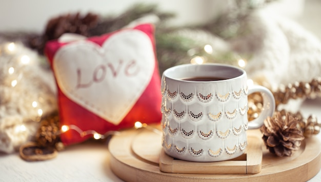 Cozy winter composition with a cup of tea on a blurred background with bokeh. concept of winter comfort and warmth.