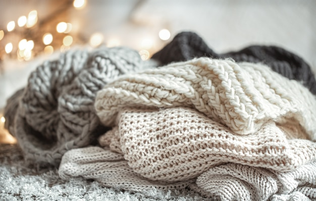 Cozy winter composition with knitted items on a blurred background with bokeh.