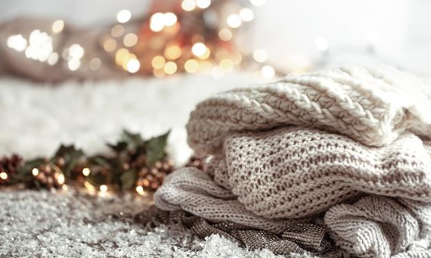 Уютная зимняя композиция с вязанными предметами на размытом фоне