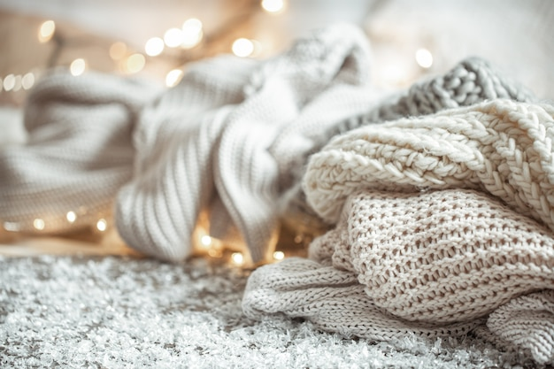Cozy winter composition with light knitted items on a blurred background with bokeh.