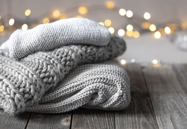 Cozy winter composition with a stack of knitted items on a blurred background with bokeh, copy space.