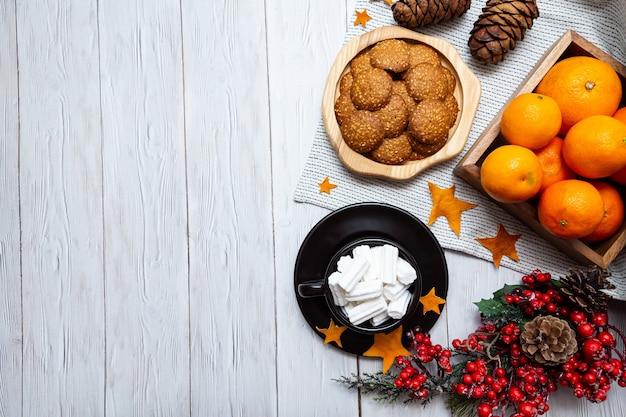 Уютная зимняя композиция с мандаринами, печеньем, шоколадом, шишками и чашкой маршмеллоу