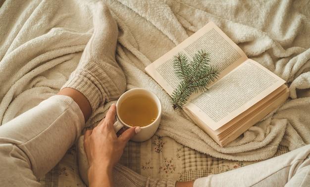 居心地の良い冬の夜、暖かいウールの靴下。女性は白い毛むくじゃらの毛布と本を読んで足を横になっています。居心地の良いレジャーシーン。本のテキストが読めません。家でのんびり女性。快適なライフスタイル。