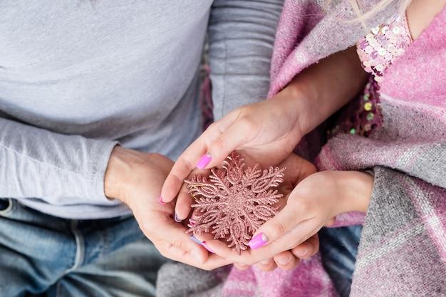 아늑한 겨울 가족 시간. 따뜻한 담요로 덮여 손에 장미 골드 반짝이 눈송이를 들고 남자와 여자