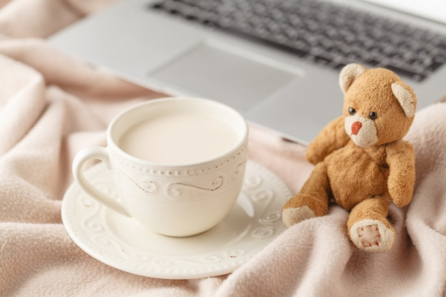 Cozy winter home background, cup of hot coffee with milk, warm knitted sweater on white bed background, vintage tone. lifestyle concept
