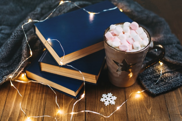 Cozy winter home. big cup of cocoa with marshmallows, warm knitted sweater, books, christmas garland on a wooden table. atmosphere of winter evening.