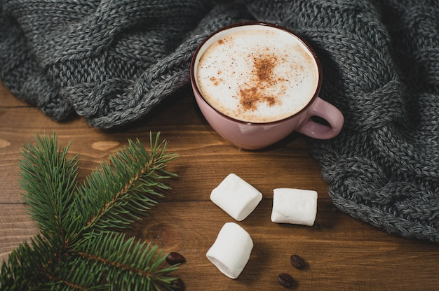Cozy winter home. cup of cocoa with marshmallow, warm knitted scarf and sprig of christmas tree, coffee beans on brown wooden table.