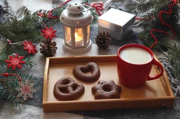 トレイとクリスマスツリーの枝にミルク釉ジンジャーブレッドの赤いカップと居心地の良い冬のポストカード