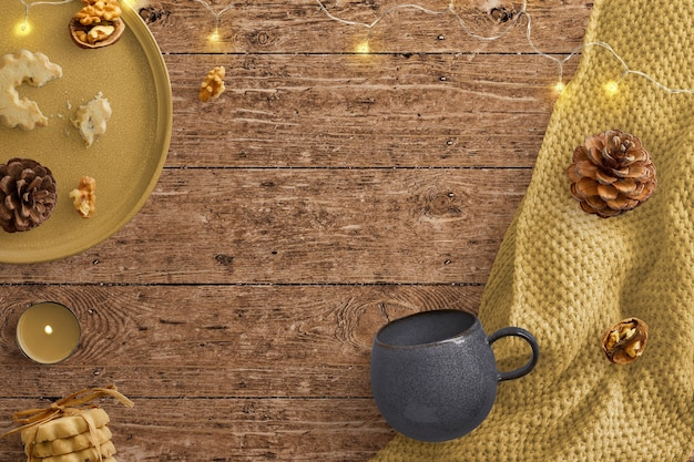 フェアリーライト、毛布、ビスケット、木製の背景にマグカップと居心地の良い冬景色