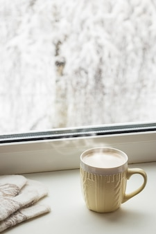窓の外の雪に覆われた木の反対側の窓辺にある居心地の良い冬の静物カップのホットコーヒーと暖かいミトン