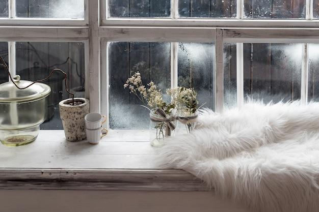아늑한 겨울 정물. 빈티지 주방 창턱에 말린 식물, 작은 커피 컵 및 따뜻한 모피. 아늑한 집 개념에서 겨울 시간을 보내는 겨울 시즌.