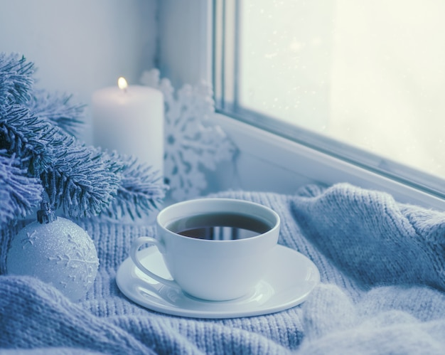Cozy winter still life: mug of hot tea and book with warm plaid on windowsill against snow landscape from outside.