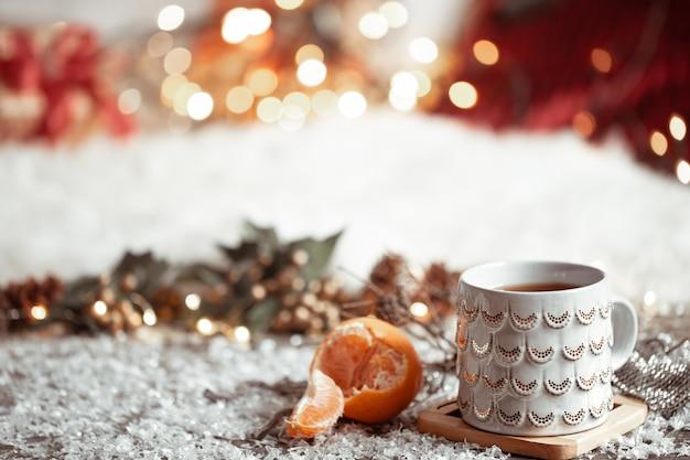 Уютная зимняя стенка с красивой чашкой и мандарином с боке.
