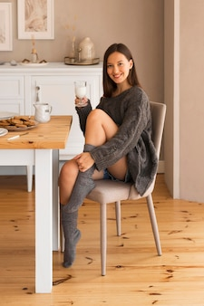 Cozy woman on chair holding glass of milk