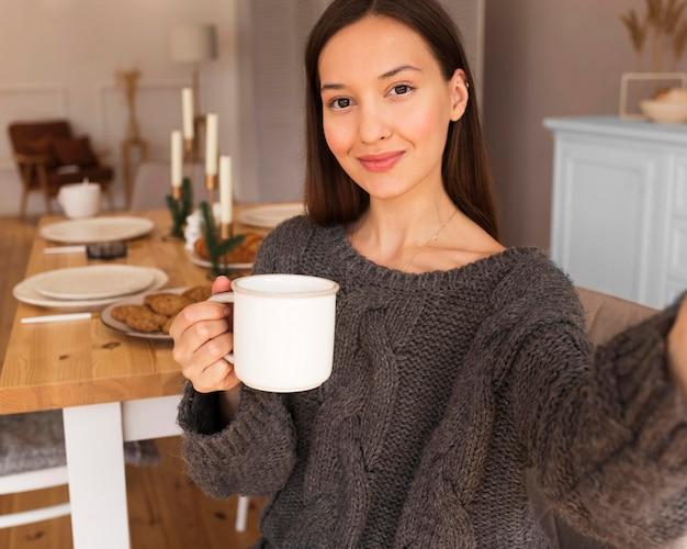 マグカップを持って自分撮りをしている居心地の良い女性